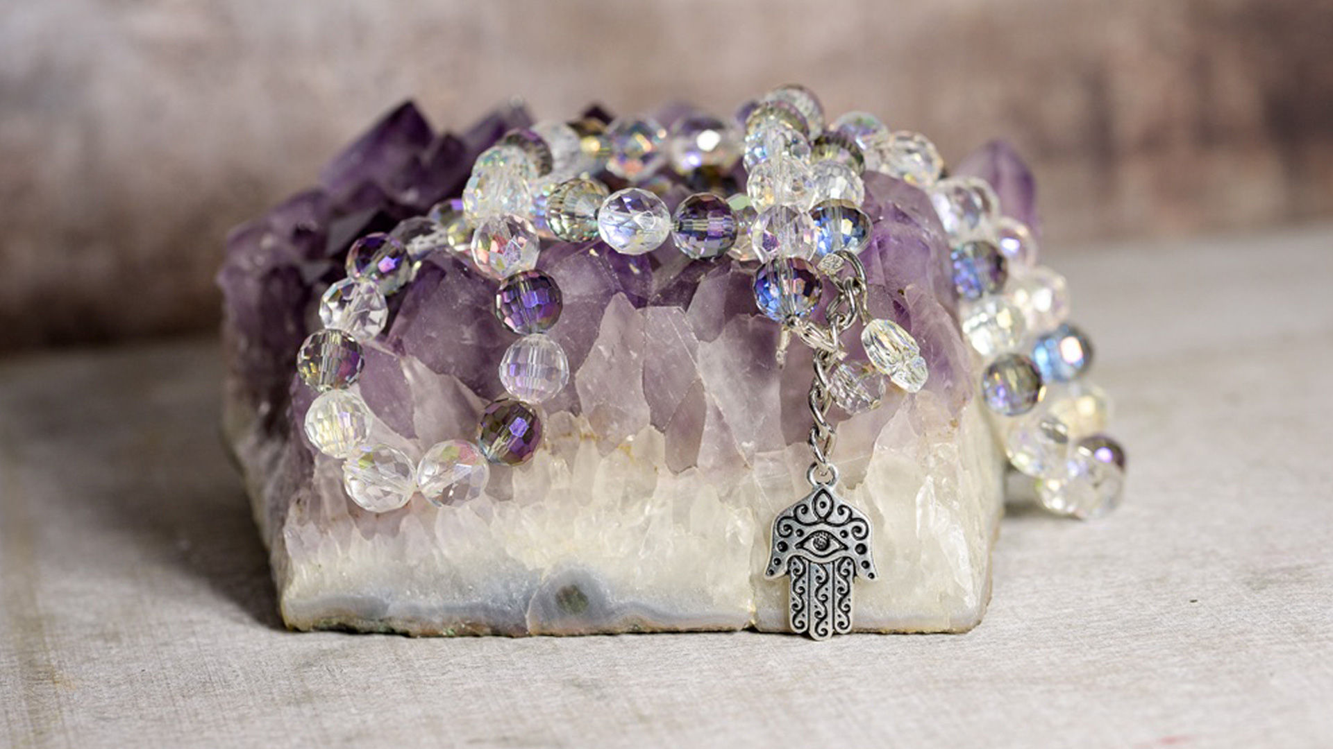 Khamsa BellyBelt with light purple and clear beads and a silver Khamsa pendent on a purple gemstone rock.