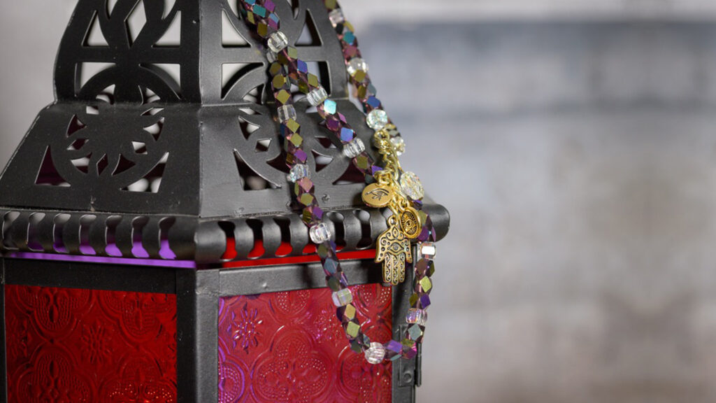 Khamsa BellyBelt with colourful beads and a gold Khamsa and evil eye pendent hanging on a lantern.