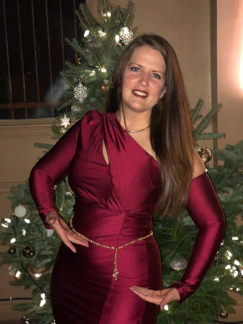 Customer posing in a satin maroon outfit wearing a golden bellybelt in front of a holiday tree.