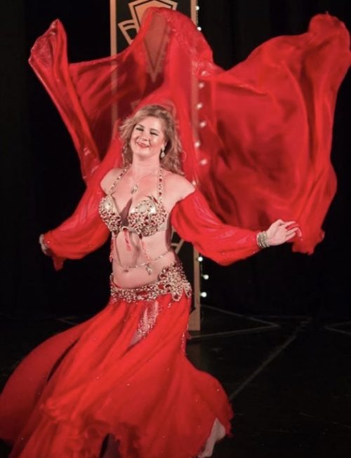 Bellydancer posing in a red outfit with a red fabric blowing in the wind wearing a clear and golden bellybelt.