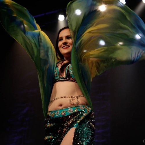 Bellydancer dancing in a green outfit with a colourful shawl wearing a gold and custom beaded bellybelt.
