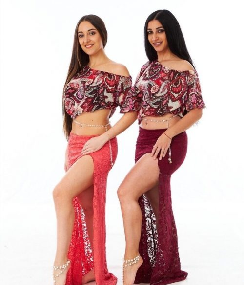 Two dancers posing in matching outfits wearing long drop chain bellybelts.