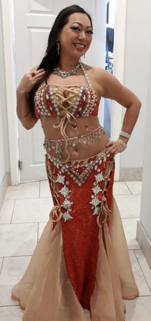 Bellydancer posing in a glimmery red outfit wearing a bellybelt with large dangling pendents.