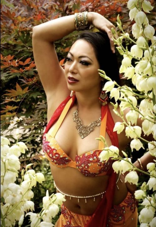A bellydancer with a red and orange outfit posing with a bellybelt that has hanging charms.