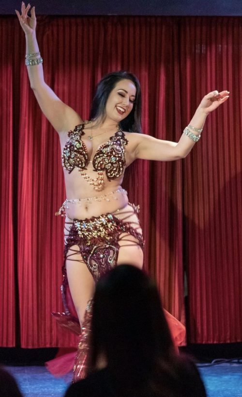 Dancer on stage in a deep maroon and glittery outfit wearing a bellybelt with clear beads and drop down pendents.