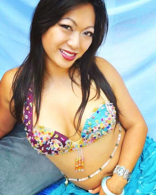 Closeup of a model in a blue bellydance outfit wearing a white and dark beaded custom bellybelt.