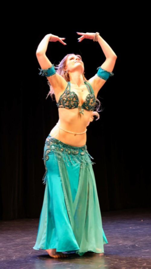 Bellydancer in an aqua outfit on stage dancing while wearing a bellybelt.
