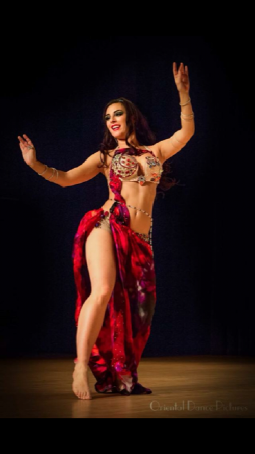 Dancer on stage wearing a red outfit wearing a clear beaded bellybelt.