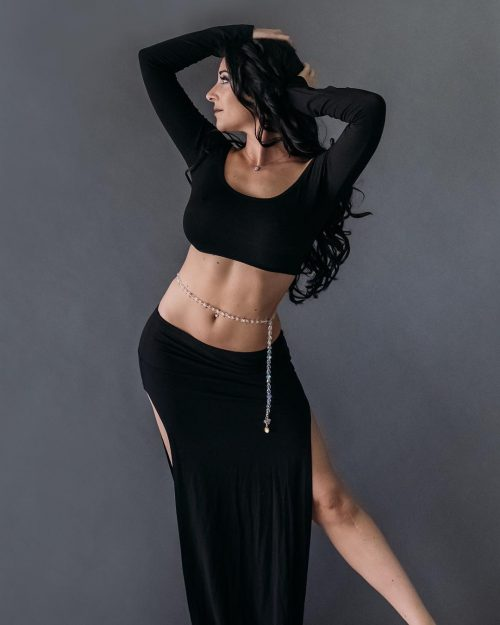 Dancer posing in a black outfit wearing a clear and light beaded bellybelt.