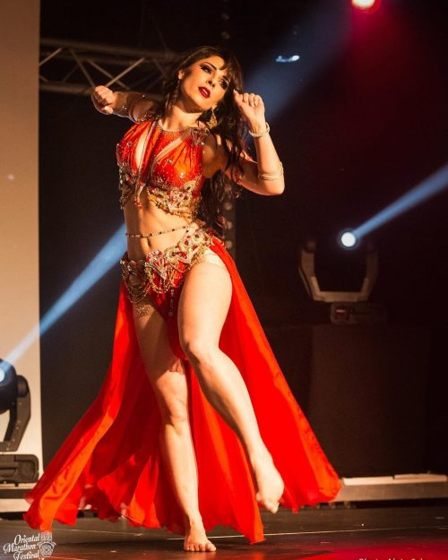 Bellydancer dancing in a red outfit on stage while wearing a custom gold beaded bellybelt.