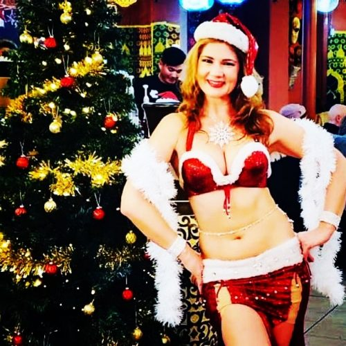 Customer smiling wearing a Santa hat and red and white bellydance outfit next to a holiday tree, wearing a bellybelt.