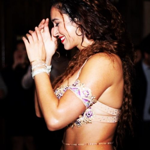 Side profile of a bellydancer smiling wearing a gold and purple outfit with a bellybelt on their waist.