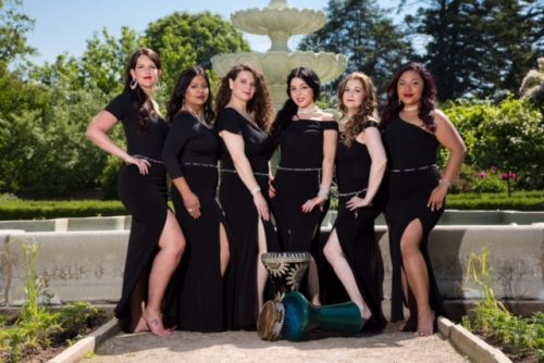 Group photo of six dancers wearing black long dresses in front of a fountain while all wearing clear beaded bellybelts.