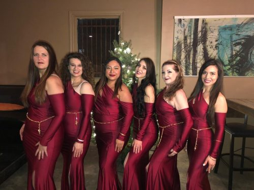 Group photo of six bellydancers wearing satin maroon dresses and bellybelts on top in gold.