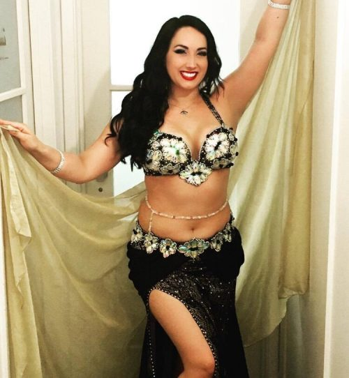 Bellydancer in a dark outfit with golden wrap wearing a gold and clear beaded bellybelt.