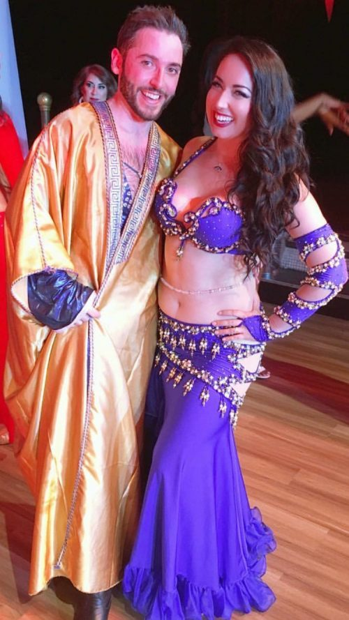 Bellydancer in a purple outfit smiling with a male dancer while wearing a clear beaded bellybelt.