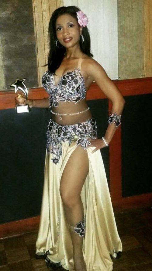 Dancer holding a trophy in a gold and black outfit while wearing a clear beaded bellybelt.