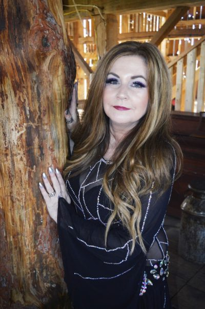 Leann leaning against a tree trunk, wearing a dark purple dress, with long dirty blonde hair.